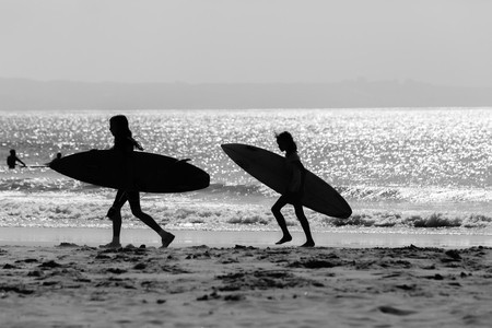 Surfing young girls silhouetted in black and white unidentified walking beach ocean waterline with surfboards.
