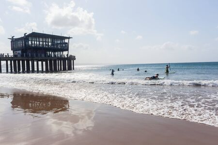 Durban south beach with people silhouetted swimming surfing next to pier jetty ocean horizon landscape.