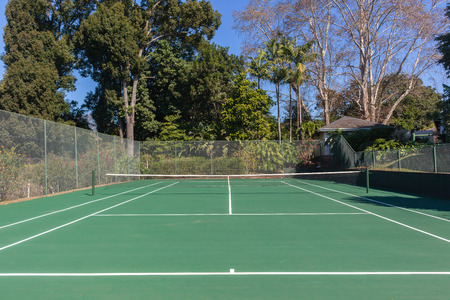 Tennis court green hard surface private secluded garden landscape.