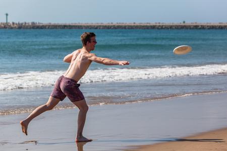Teenagers boy throwing frisbee action on beach ocean waterline.
