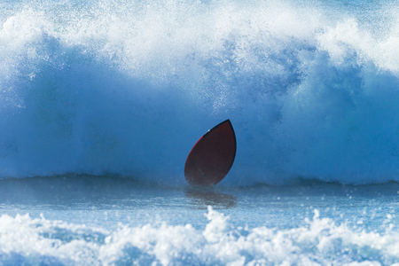 Surfer surfing crashing leaves board and ocean wave.