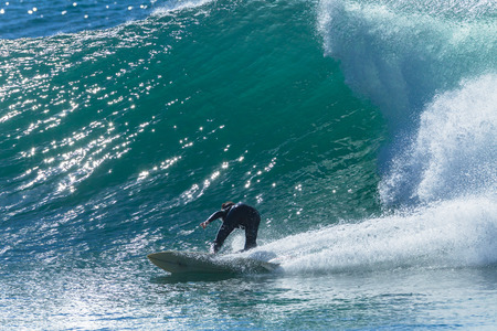 Surfer unidentified surfing catching ocean wave action photo