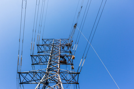 Electricians high up hanging suspended on electrical steel tower installing new high voltage electricity power lines