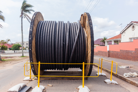 Construction Electrical new high voltage power cables drum been installed in underground Trenches.