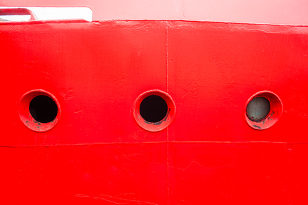 Ship boat bow with cabin portholes with red paint hull closeup in harbor.