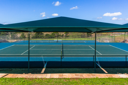 Tennis courts outdoors summer spectator seating with shade awnings photo. Stock Photo