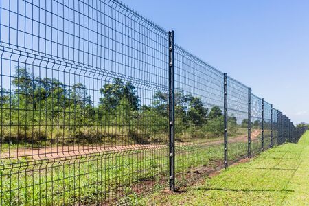 vandalism: Boundary Fence steel erected on property in countryside landscape. Stock Photo