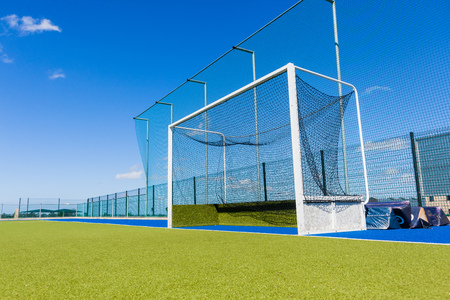 Hockey field goals nets astro turf surface field outdoors countryside.