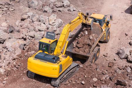 Industrial excavator machine loading construction truck vehicle heavy rock earthworks.