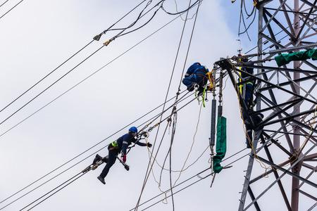 Elektriciens die op staalkabels hoog boven grond hangen die aan de elektrische lijnen van de kabelmacht op staaltoren werken.