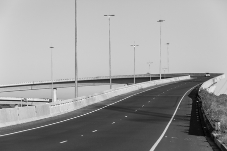 Road highway overhead flyover overpass with vehicle on ramp entry exit structures in black and white. Stock Photo