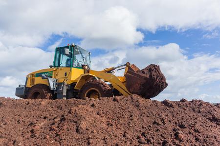 Industriële van de de bulldozerlader van grondwerken de emmermachine op de close-up van de bouwconstructieplaats.