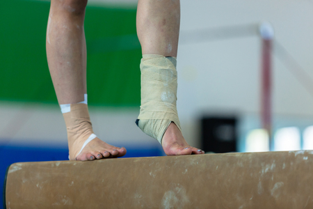 Gymnastics teenager girl unidentified on balance beam apparatus closeup abstract ankles leg foot toe nail injury strapped bandages tape still performing competition routine. Reklamní fotografie