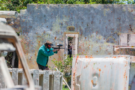 Paintball game action arena player air gun in old broken house outdoors countryside arena. Foto de archivo