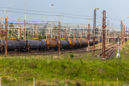 Train with cargo pulls into station transporting jet fuel tankers. Stock Photo