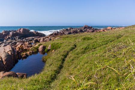 Rocky grass ocean wave coastline holiday landscape. Stock Photo