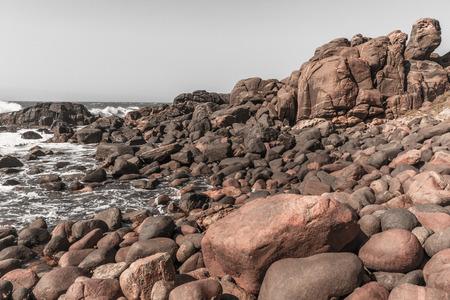 Rocky coastline boulders along ocean in vintage photo tones Stock Photo