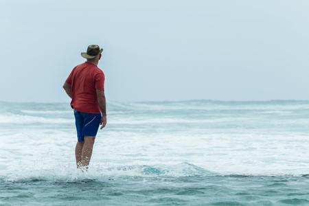 Man on beach tidal pool wall watching  ocean waves power crashing on overcast windy day. Stock Photo