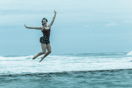Teenager girl holidays jumping on beach tidal pool wall with overcast ocean waves on horizon. Stock Photo