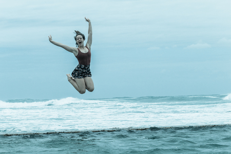 Teenager girl happy holidays  jumping on beach tidal pool wall with overcast ocean waves on horizon. Stock Photo