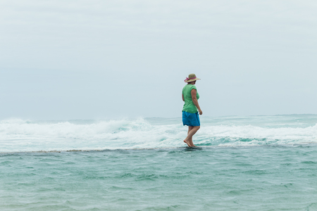 Woman walking beach tidal pool wall watching  ocean waves power crashing on overcast windy day.