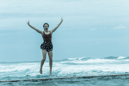 Teenager girl  jumping on beach tidal pool wall with overcast ocean waves on horizon.