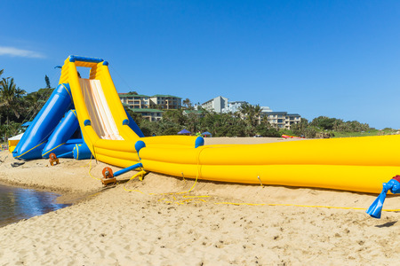 Beach ocean public amusement  thrill rides down high water slide inflated structure during summer holidays. Stock Photo