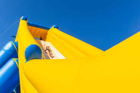 Teen girl caucasian thrill ride down high water slide inflated amusement structure on beach summer holidays. Stock Photo