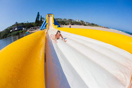 Teen girl caucasian thrill rides down high water slide inflated amusement structure on beach summer holidays.
