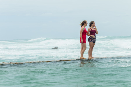 Teenager girls  beach holidays walking talking time on tidal pool wall with overcast ocean waves on horizon.