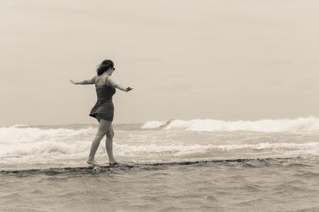 Teenager girl walking challenge balancing along  beach  tidal pool wall with overcast ocean waves on horizon. Stock Photo