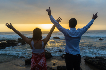 Teenagers boy girl arms up dressed white shirt  silhouetted at beach on rocks at ocean dawn sunrise.