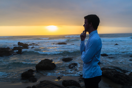 Young man dressed white shirt black longs looking over ocean waves horizon at dawn sunrise silhouetted closeup photo.