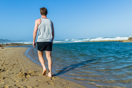 Young man walking beach sands next to ocean waves tidal swimming pool afternoon landscape Stock Photo