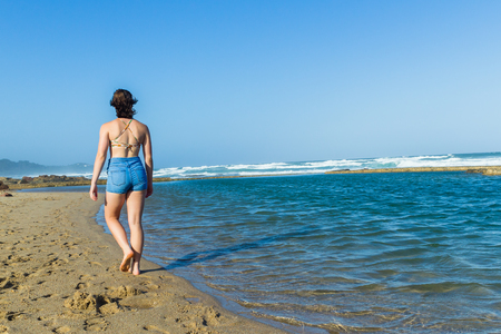 Young Tenn Girl walking beach sands next to ocean waves tidal swimming pool afternoon landscape