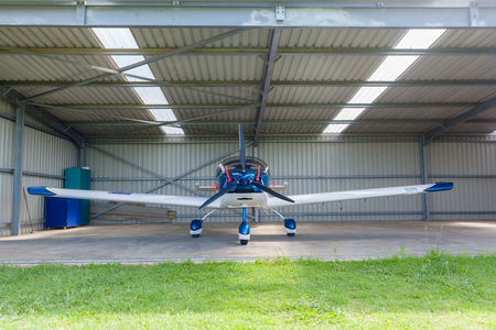 Aircraft two seater plane inside hangar garage in remote countryside. Stock Photo