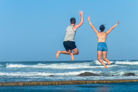 Girl boy teenagers jump leaping on beach ocean tidal swimming pool waves holiday landscape. Stock Photo