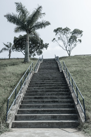 Long concrete staircase of steps up hillside with hand railing structure outdoors aged bleach photo.