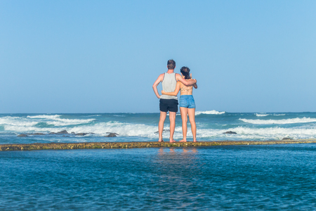 Girl boy teenagers standing together on beach ocean tidal swimming pool wall watching waves holiday landscape. Stock Photo