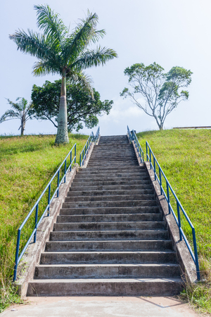 Long concrete staircase of steps up hillside with hand railing structure outdoors.