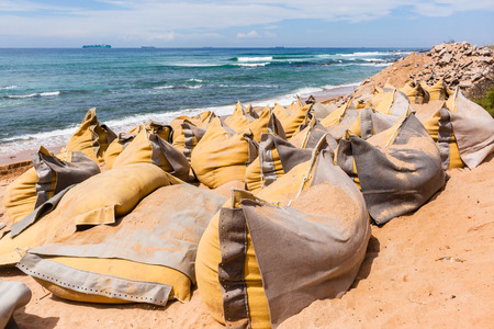 Construction on beach water line coastline building repairs with sandbags buffer on sand dunes to protect road buildings from ocean storms.
