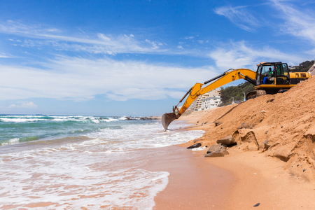 Construction excavators machines on beach water line coastline building repairs with sandbags buffer on sand dunes to protect road from ocean storms.