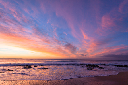 Beach Ocean coastline with dawn light reflections of scenic blue pink yellow colors  on  cirrus clouds.