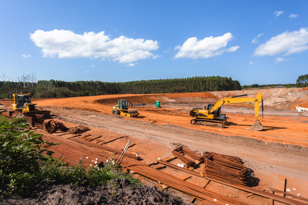 Construction industrial earthworks machines for new bridge structure over countryside highway