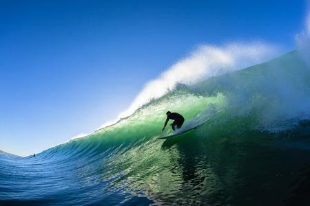 Surfen surfer buis rijdt oceaan golf ochtend silhouet niet-geïdentificeerde waterfoto actief