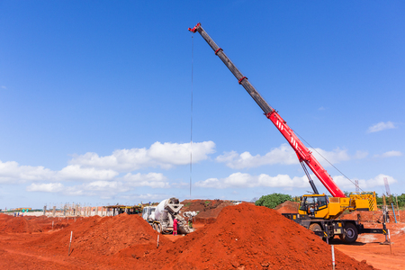 Construction industrial building site mobile crane and concrete truck doing cement bucket delivery to foundations.