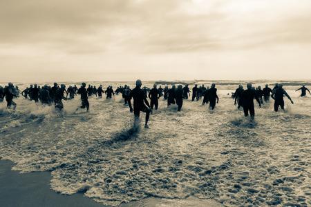 Triathlon beach athletes silhouetted swim race start in ocean water course at dawn sunrise