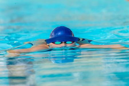 Swimming race dive surfacing young girl head on photo face to face water split line on face head goggles frozen water curve Stock Photo