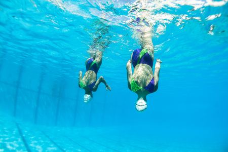 Aquatic synchronized unidentified girl swimmers dance moves closeup underwater photo action. Stockfoto