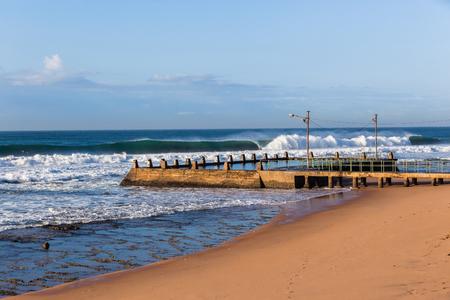 Ocean waves breaking crashing front of tidal swimming pool beach landscape.